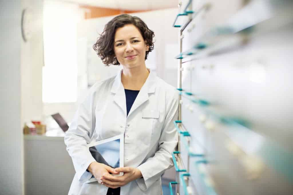 Portrait of confident young female pharmacist leaning to a medicine shelf with a digital tablet.