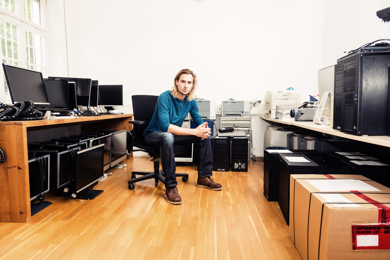 An IT professional sits with a variety of technology assets.
