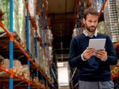 A manager uses inventory management software to keep his warehouse organized and profitable.