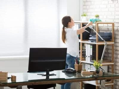 A woman cleans her office.