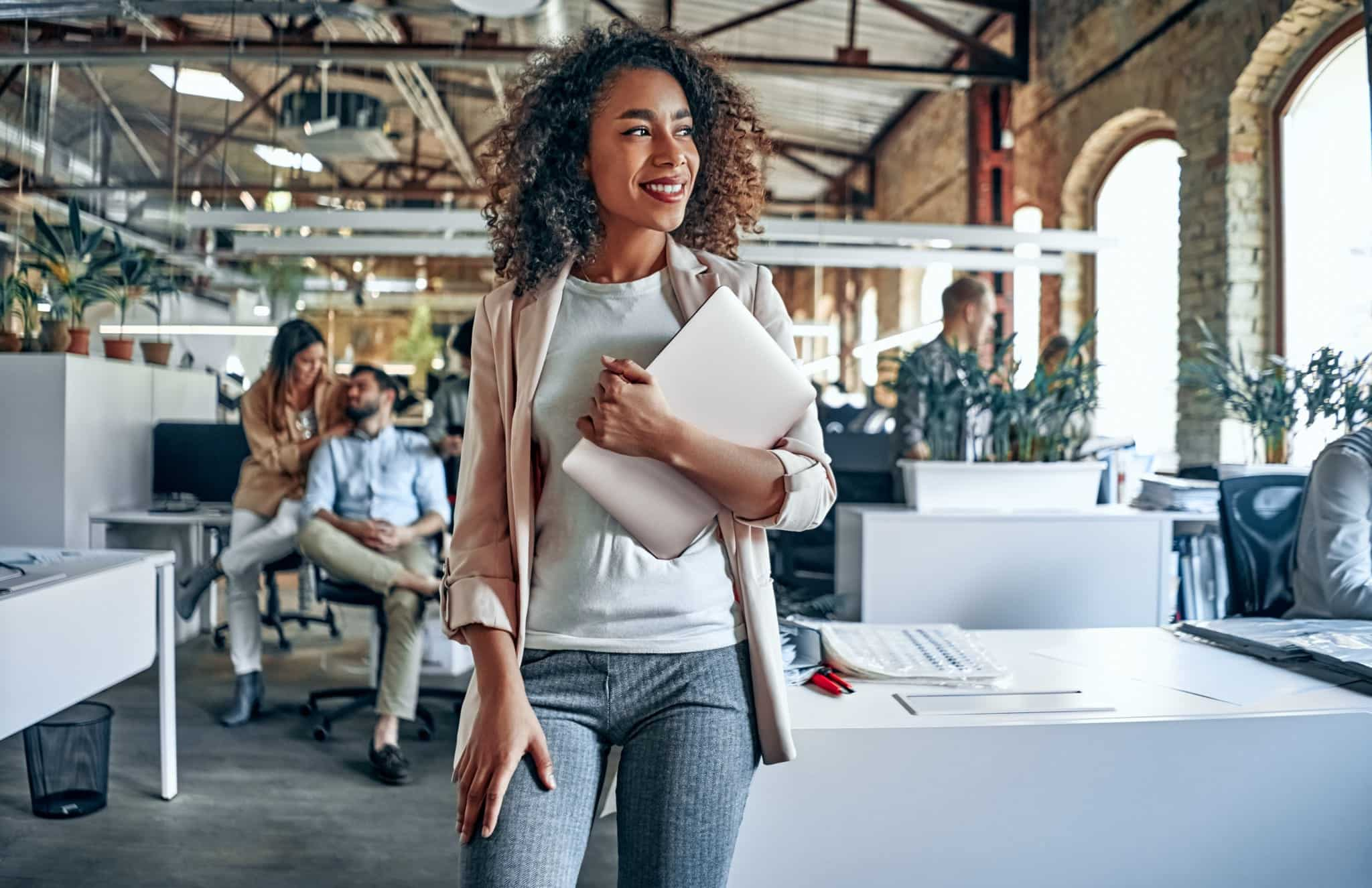 A woman walks through her office carrying a laptop while smiling.