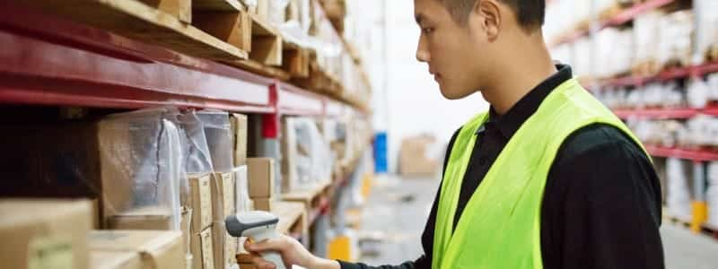 A man in a neon vest takes inventory using a barcode scanner.